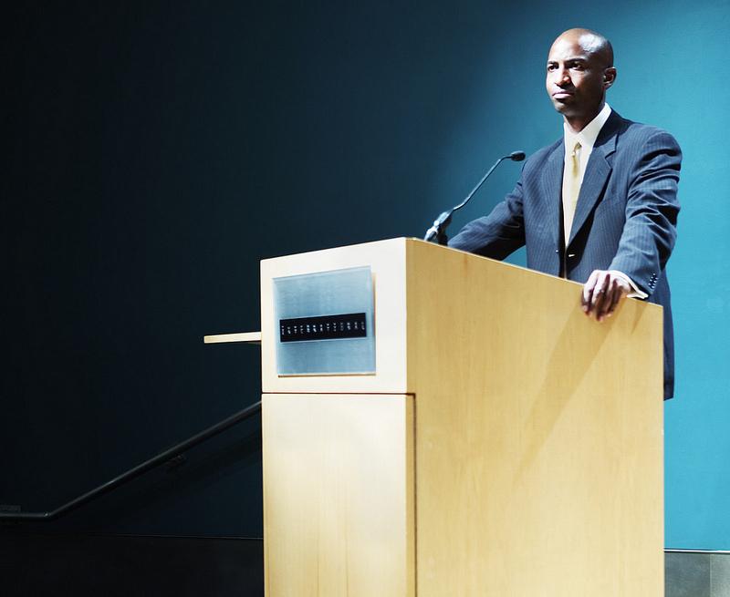 Labour leadership presentation skills man at podium Confident presenter.