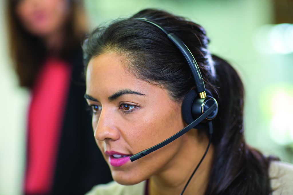 telephone skills training courses lady with headset in contact centre.
