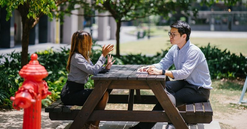 how to be assertive, colleagues at a bench, pink elephant communications